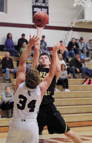 T-R PHOTO BY STEPHEN KOENIGSFELD • David Disney shoots over Grundy Center's Bryce Flater during the second half of Friday night's game. Disney had a team-high 17 points in the 60-55 win at Grundy Center.