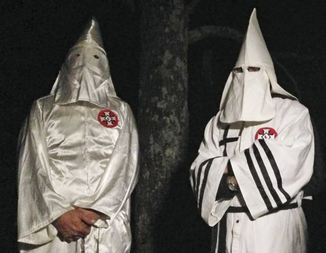 "AP PHOTO In this Dec. 2 photo, two masked Ku Klux Klansmen stand on a muddy dirt road during an interview near Pelham, N.C. The KKK and other white extremist groups don't like being called ""white supremacists,"" a phrase that dates to the earliest days of white racist movements in the United States."