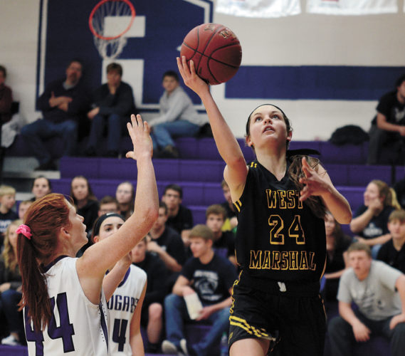 T-R PHOTO BY STEPHEN KOENIGSFELD • West Marshall's Isabelle Gradwell (24) shoots a layup over AGWSR's Maddie Brandt (44) during Friday night's NICL West Conference match in Ackley. Gradwell had 16 points in the Trojans' 68-49 win.
