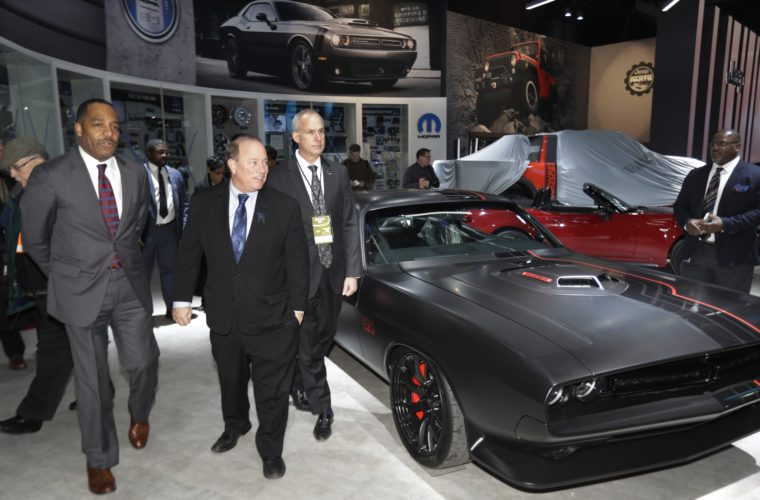 Detroit Mayor Mike Duggan, center, and North American International Auto Show Chairman Sam Slaughter, right, are given a tour of the Mopar area from Ron Stallworth, left, of Fiat Chrysler Automobiles, Friday, Jan. 6, 2017, in Detroit. The show opens to the media on Monday, Jan. 9 and to the public on Jan. 14. (AP Photo/Carlos Osorio)