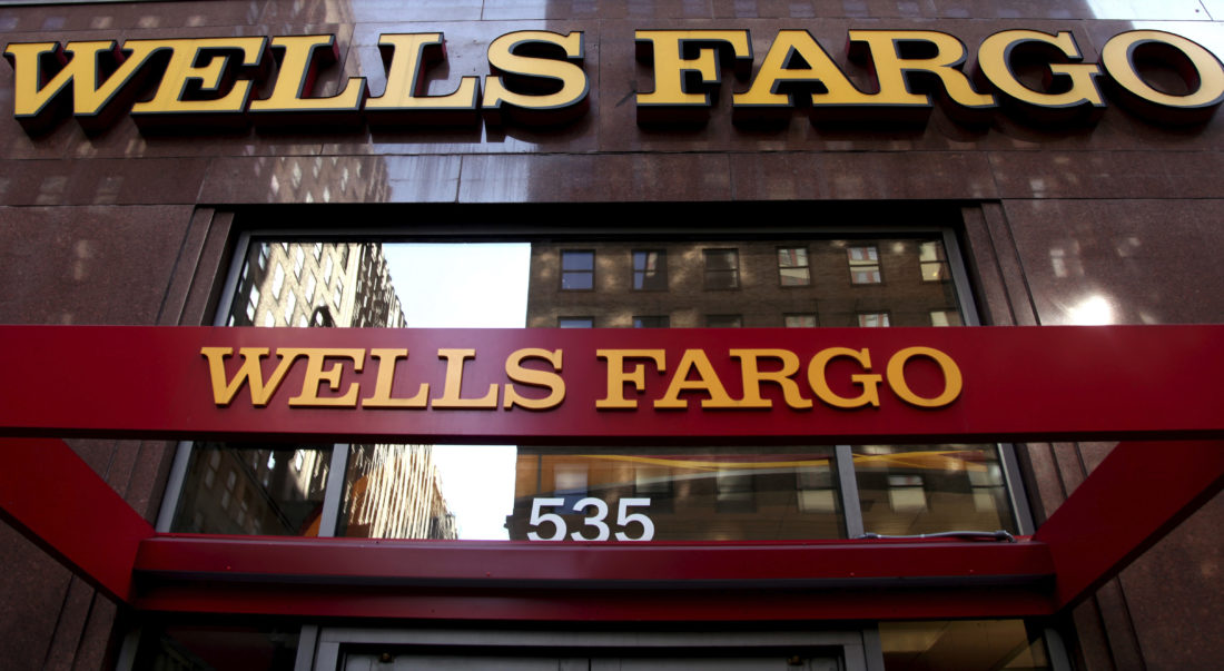 AP PHOTO This May 6, 2012, file photo, shows a Wells Fargo sign at a branch in New York. Wells Fargo announced Tuesday, it is completely restructuring how it pays tellers and other bank branch employees after a scandal over its aggressive sales practices.