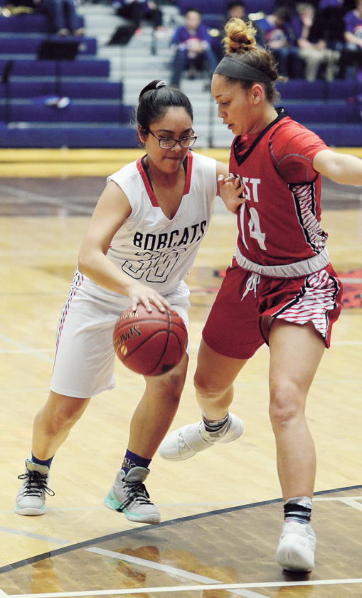 T-R PHOTO BY STEPHEN KOENIGSFELD • Vanessa Vergara (30) tries to drive past Des Moines East's Tiana Ziegler (14) during the first half of Tuesday night's game at the Roundhouse. The Bobcats fell, 62-22.