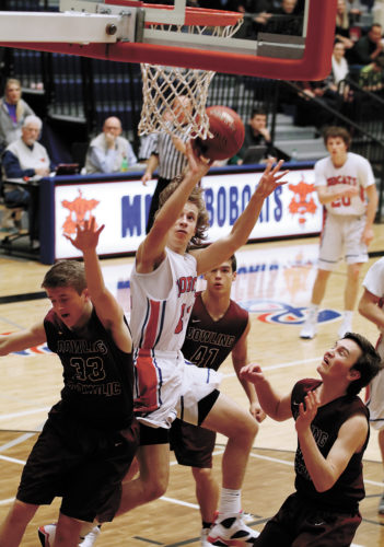 T-R PHOTO BY ADAM RING • Marshalltown basketball player Blake Linsenmeyer gets a shot off in the second half against Dowling Catholic Friday night inside the Roundhouse. Dowling ran away from the Bobcats, taking the CIML Iowa Conference matchup 79-28.