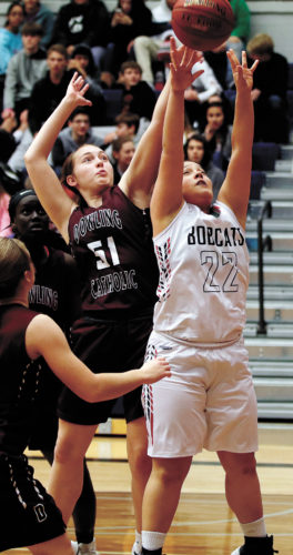T-R PHOTO BY ADAM RING • Marshalltown basketball player Luz Morciego (22) puts up a shot contested by Dowling Catholic's Allie Hittner (51) in the second half Friday night inside the Roundhouse.