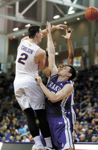 AP PHOTO • Northern Iowa's Klint Carlson (2) passes the ball over the Drake defense in the second half of a Missouri Valley Conference basketball game Sunday in Cedar Falls.