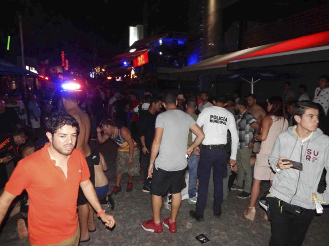 In this photo released by Por Esto de Quintana Roo, people react after a shooting at the outdoor venue Blue Parrot nightclub in the Caribbean coast resort of Playa del Carmen, Mexico, early Monday, Jan. 16, 2017. The deadly shooting occurred in the early morning hours at the club while it was hosting part of the BPM electronic music festival, according to police. (Por Esto de Quintana Roo, via AP)