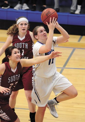 T-R PHOTO BY STEPHEN KOENIGSFELD • Megan Swanson (11) drives in for a layup between defenders during the first half of Tuesday night's game against South Hamilton in Reinbeck. Swanson had two points in the 54-28 loss.