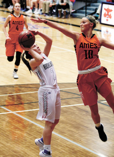 T-R PHOTO BY ADAM RING • Marshalltown girls' basketball player Alyvia Chadderdon, left, has her shot contested by Ames' Kelly Friedrich Tuesday at the Roundhouse. Ames topped the Bobcats, 60-19.