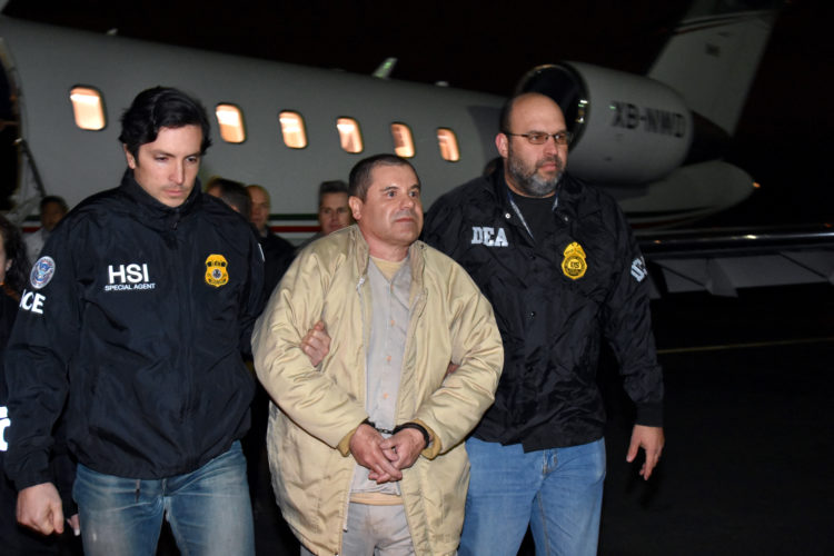 """AP PHOTO In this photo provided U.S. law enforcement, authorities escort Joaquin """"El Chapo"""" Guzman, center, from a plane to a waiting caravan of SUVs at Long Island MacArthur Airport on Thursday, in Ronkonkoma, N.Y."""