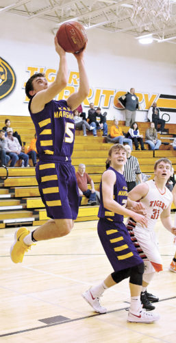 T-R PHOTO BY DALE PUUMALA • East Marshall senior Dru Boliver, left, goes over 1,000 points for his career with this basket against Iowa Valley on Thursday night in Marengo. Boliver ended the game with nine points to settle at 1,001 for his career after the Mustangs' 74-29 win.