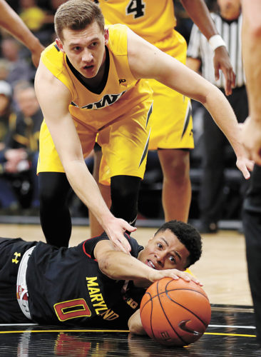 AP PHOTO • Maryland's Anthony Cowan (0) grabs a loose ball in front of Iowa guard Jordan Bohannon during the second half of Thursday's Big Ten Conference game in Iowa City. Maryland won 84-76.