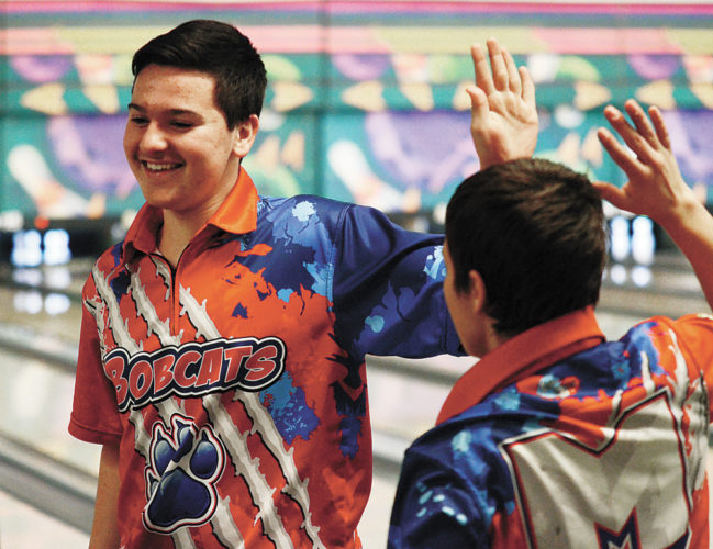 T-R PHOTO BY STEPHEN KOENIGSFELD • Kamrin Chizek high-fives MHS bowling teammate Ray Wiegand, right, after picking up a difficult split during the Bobcats' dual with Ankeny on Thursday. The Bobcats won 3,020-2,729.