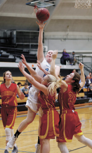 T-R PHOTO BY ADAM RING • South Tama County girls' basketball player Kaitlyn Berger gets a shot off in the second quarter despite a double team from Marion Thursday night in Tama. STC fell against the Class 4A No. 2 Indians, 74-25.