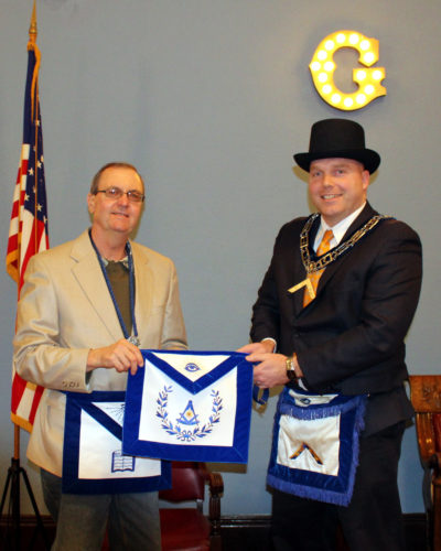 CONTRIBUTED PHOTO Brandon Ruopp, newly installed worshipful master of Marshall Lodge No. 108, A.F. & A.M., (right) presents Steven Smith with his past master apron.
