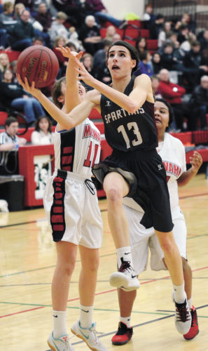 t-r photo by Ross thede Hailey Wallis (13) drives in for a layup, contested by Meskwaki's Payton Tahahwah, during the Spartans 51-40 win Monday night.