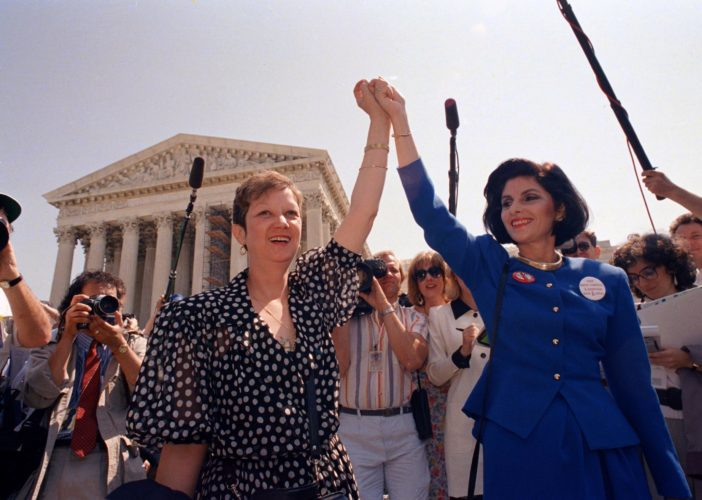AP PHOTO In this April 26, 1989 file photo, Norma McCorvey, Jane Roe in the 1973 court case, left, and her attorney Gloria Allred hold hands as they leave the Supreme Court building in Washington. McCorvey died at an assisted living center in Katy, Texas on Saturday.