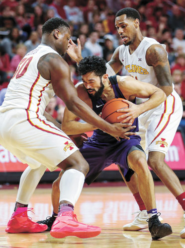 AP PHOTO • TCU guard Alex Robinson is trapped by Iowa State defenders Deonte Burton, left, and Monte Morris during the second half of a college basketball game Saturday night at Hilton Coliseum in Ames.