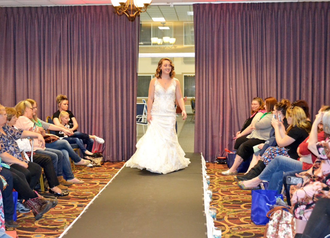T-R PHOTO BY SARA JORDAN-HEINTZ During the 10th annual Times-Republican Bridal Expo on Sunday afternoon, a bridal fashion show was held. It featured wedding dresses, bridesmaid dresses, tuxes and flower girl apparel, showcased by Heart to Heart Bridal of North Liberty, Impress Bridal of Newton and Willard's Furs and Fashions of Marshalltown. Pictured is Kylie Smith modeling an Allure style 9401 dress from Heart to Heart Bridal.
