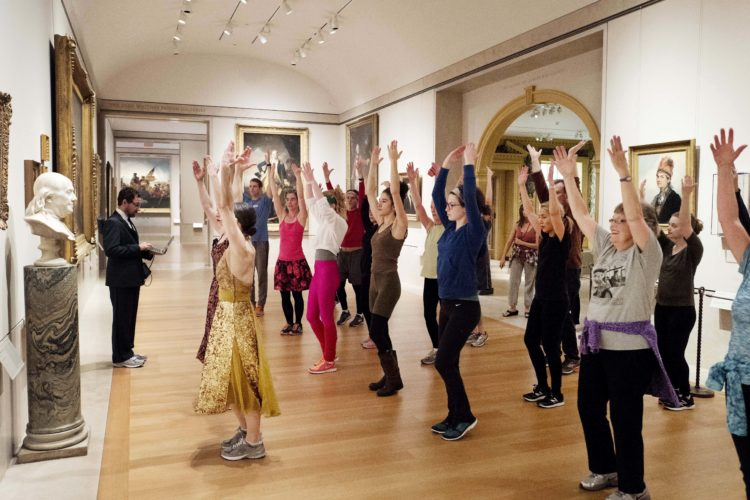 In this Feb. 10, 2017 photo, an exercise group works in front of a bust of Benjamin Franklin at the Metropolitan Museum of Art in New York. New York City's cavernous museum has been holding lively morning workout sessions this winter amid its prized masterpieces.  (AP Photo/Mark Lennihan)
