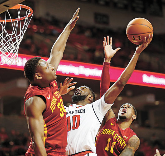 AP PHOTO • Texas Tech's Niem Stevenson (10) tries to shoot the ball over Iowa State's Deonte Burton (30) and Monte Morris (11) during a Big 12 Conference basketball game Monday in Lubbock, Texas.