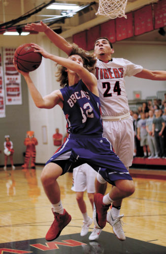 T-R PHOTO BY ADAM RING • Marshalltown's Blake Linsenmeyer (32) has his shot contested by Cedar Falls' Isaiah Johnson (24) in the first quarter of Monday's Class 4A Substate 3 opener in Cedar Falls. MHS fell to the Tigers 73-43.