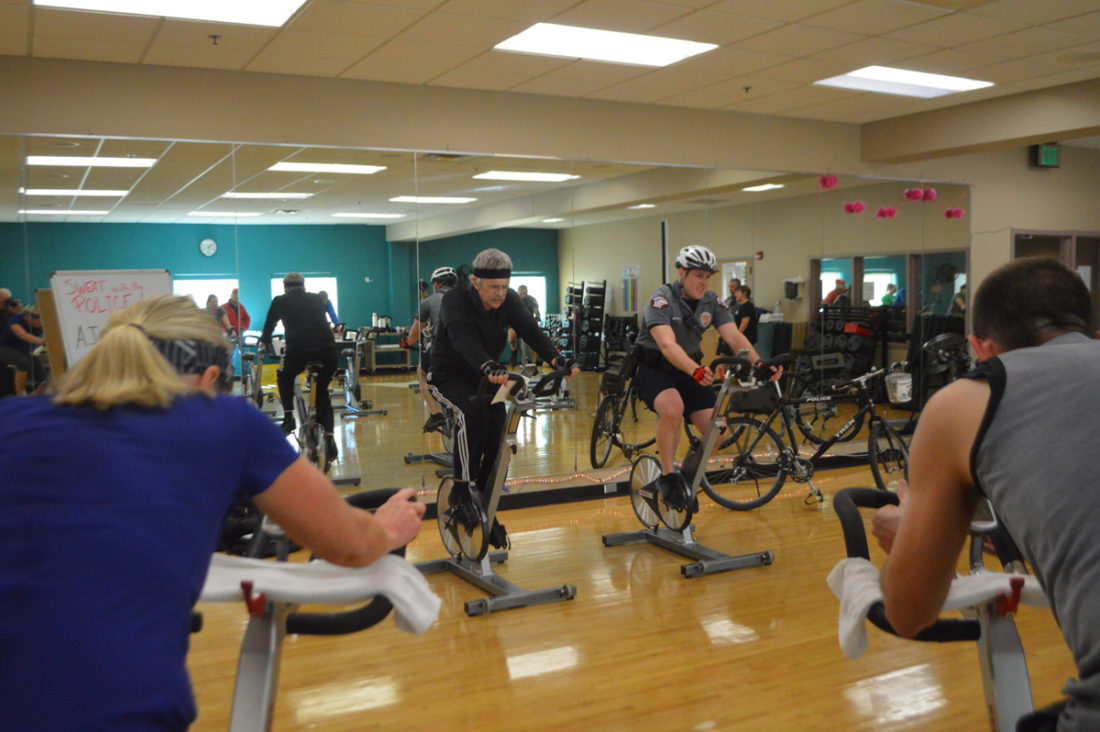 "T-R PHOTO By MIKE DONAHEY Marshalltown YMCA-YWCA Group Bicycling Instructor Rob Cooper, left, is joined by Marshalltown Police Officer A.J. Accola during the ""Sweat with the Police"" event in Studio 1 at the Y Saturday morning."