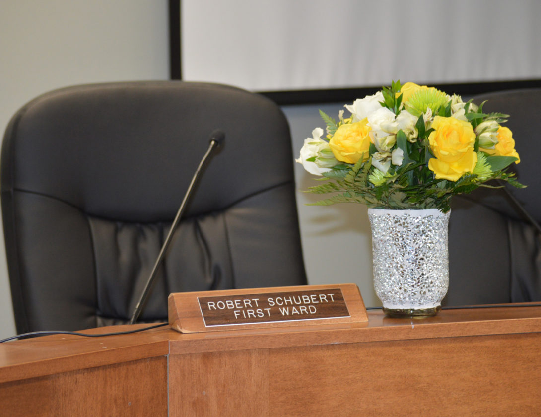 T-R PHOTO By MIKE DONAHEY Pictured is the late First Ward Councilor Bob Schubert's chair and a bouquet of flowers to honor his memory in city council chambers Monday night.  Schubert, 78, was found dead at his home Monday morning by Marshalltown police conducting a welfare check.  A coworker from the Marshalltown Community School District bus barn had notified the MPD when Schubert had failed to report for work.