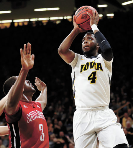 AP PHOTO • Iowa guard Isaiah Moss, right, shoots over South Dakota's Triston Simpson (3) during the first half of a first-round game in the men's National Invitation Tournament on Wednesday night at Carver-Hawkeye Arena in Iowa City. Moss scored 16 points as the Hawkeyes defeated the Coyotes 87-75.