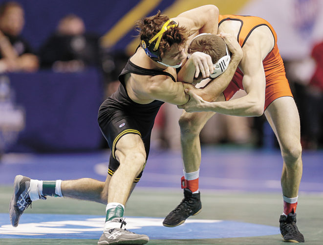 AP PHOTO • Iowa's Thomas Gilman, left, goes on the attack against Campbell's Nathan Kraisser in their 125-pound match in the second round of the NCAA Division I Wrestling Championships on Thursday in St. Louis.