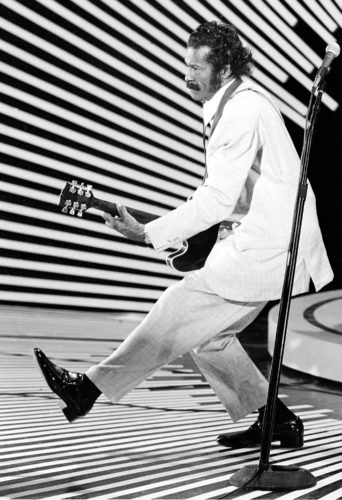 "AP PHOTO FILE - In this April 4, 1980 file photo, guitarist and singer Chuck Berry performs his ""duck walk"" as he plays his guitar on stage. On Saturday, police in Missouri said Berry has died at the age of 90."