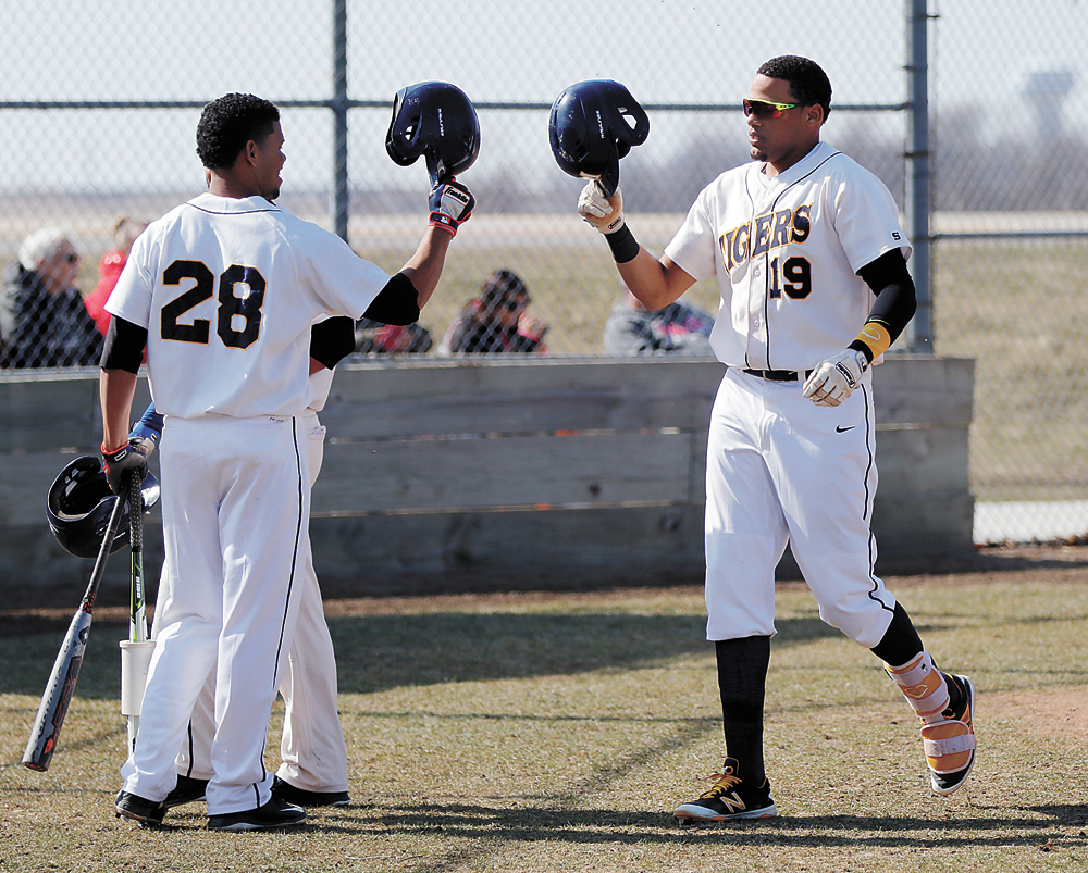 T-R PHOTO BY ADAM RING • MCC baseball players Diogen Ceballos (28) and Luis Duran (19) tap helmets in celebration of Duran hitting a home run in the second game of a doubleheader against Milwaukee Area Technical College Sunday afternoon at Shawn Williams Field. Ceballos also homered in the game as MCC swept the twinbill.