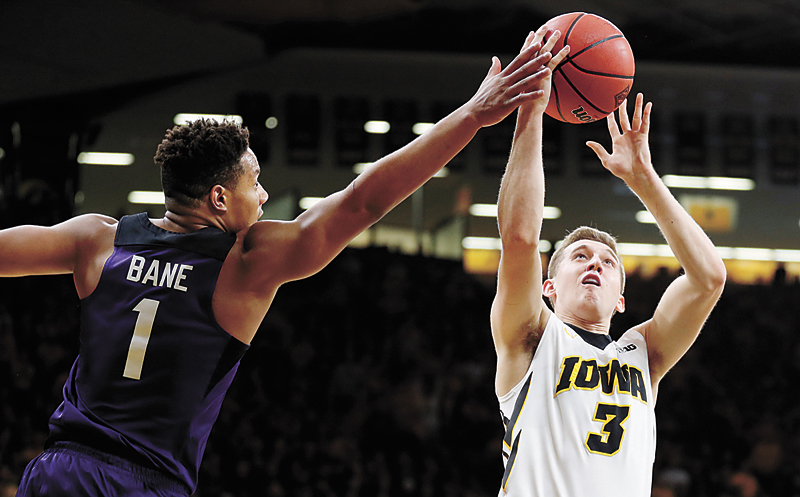 AP PHOTO • TCU guard Desmond Bane (1) tries to block a shot by Iowa guard Jordan Bohannon (3) during the second half of a second-round game in the National Invitation Tournament on Sunday afternoon at Carver-Hawkeye Arena in Iowa City. TCU won 94-92.