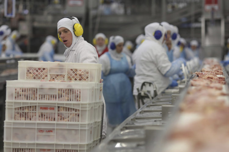 """AP PHOTO Workers prep poultry at the meatpacking company JBS, in Lapa, in the Brazilian state of Parana, Tuesday. Brazil's president said Tuesday that a scandal over sale of expired meat is an """"economic embarrassment""""."""
