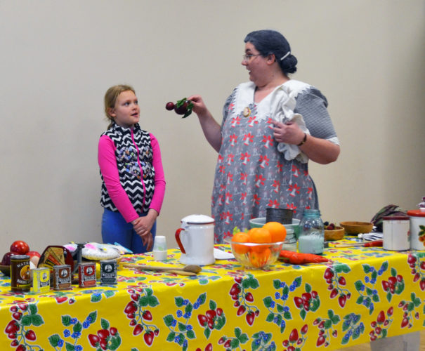 T-R PHOTO BY SARA JORDAN-HEINTZ Earlier this week at the State Center City Hall, Laura Ingalls Wilder historian Sarah Uthoff (right) stepped back in time and gave attendees a literal taste of what Wilder's life was like, in a hands-on cooking demonstration that was free and open to the public. Here young helper Ellie Kendall (left) learns how to dry plums. The event was sponsored by Humanities Iowa Speakers Bureau, and presented by the Gutekunst Public Library.