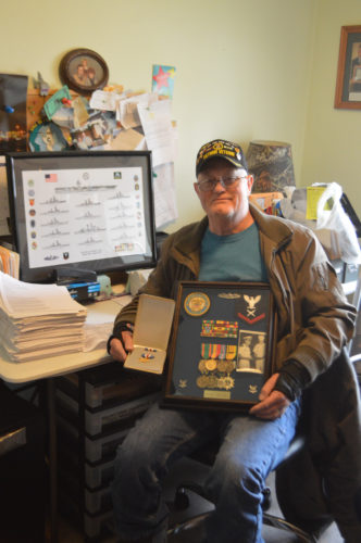 T-R PHOTO BY MIKE DONAHEY Vietnam veteran Dennis Myers of Marshalltown is pictured in his home holding many medals and commendations awarded him during Navy service as a CTO3 from 1968-72. To his immediate left is a framed print of ships he served on.