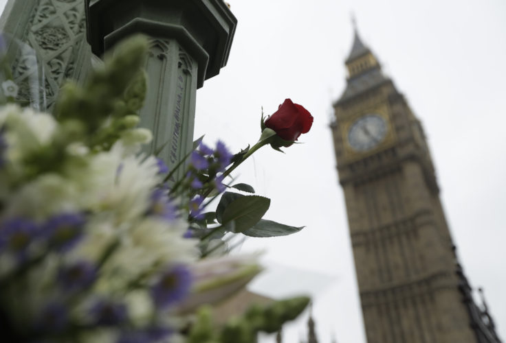 AP PHOTO Floral tributes to victims of Wednesday's attack are tied to a lamppost outside the Houses of Parliament in London, Friday.