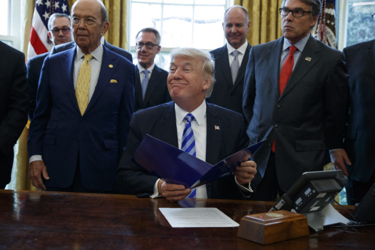 AP PHOTO President Donald Trump, flanked by Commerce Secretary Wilbur Ross, left, and Energy Secretary Rick Perry, is seen in the Oval Office of the White House in Washington Friday, during the announcing of the approval of a permit to build the Keystone XL pipeline, clearing the way for the $8 billion project.