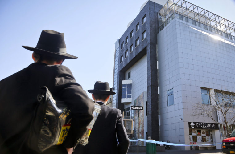 AP PHOTO In this March 9 file photo, two young men who left a nearby synagogue watch police activity outside the Jewish Children's Museum following a bomb threat in Brooklyn borough of New York.