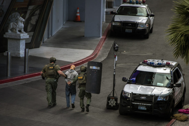 AP PHOTO A suspect is taken away after surrendering to SWAT officers after he barricaded himself inside a public bus after a fatal shooting in the vehicle earlier today shutting down the busy tourism corridor near the Cosmopolitan hotel-casino in Las Vegas, Saturday