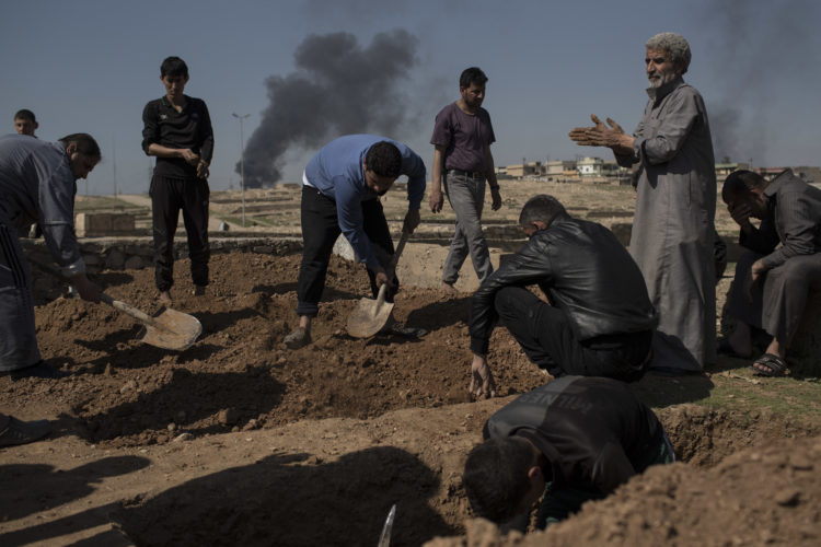 AP PHOTO Relatives and friends bury the body of Khadeer Hassan, who was killed during fighting between Iraqi security forces and Islamic State militants, on the western side of Mosul, Iraq, Saturday.