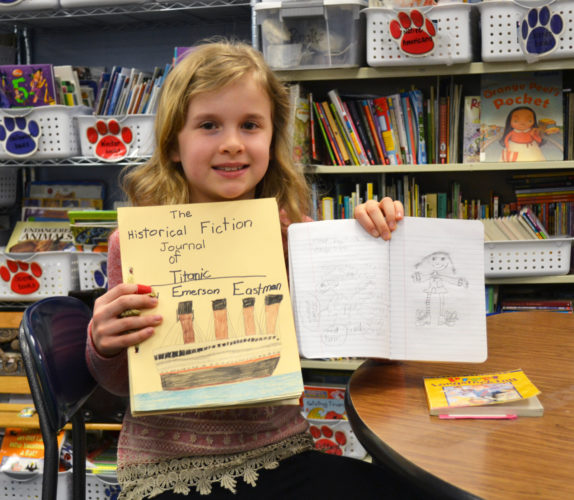 Emerson Eastman, 9, a third grader at Fisher Elementary School, enjoys reading and writing historical fiction. Here she holds the journal she made in school when she assumed the identity of the captain's daughter on the Titanic. She is also known for her drawing skills. The third grader would like to be a photographer when she grows up.