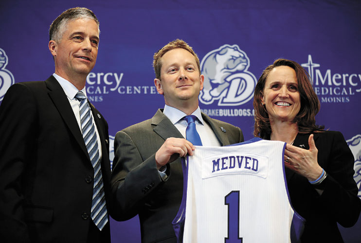 AP PHOTO • New Drake University men's basketball coach Niko Medved, center, poses with Drake President Marty Martin, left, and athletic director Sandy Hatfield Clubb during a news conference Monday in Des Moines.