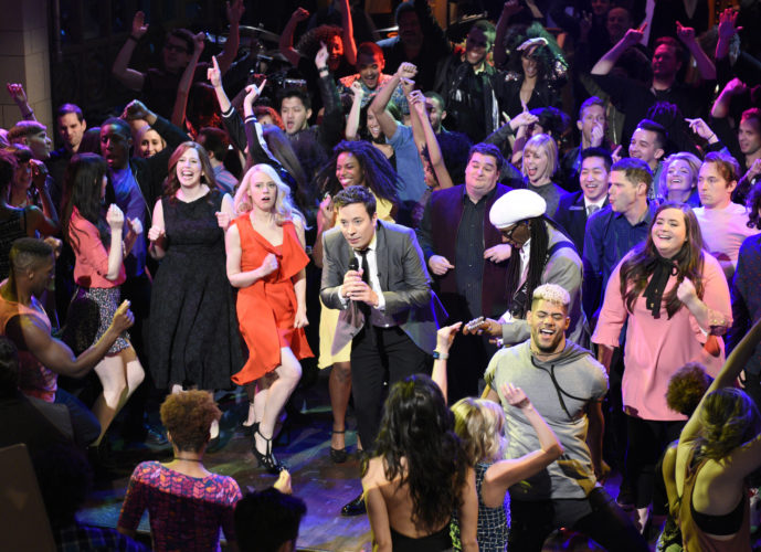 """AP PHOTO In this Saturday photo released by NBC, host Jimmy Fallon, center, performs during the opening number on """"Saturday Night Live,"""" in New York."""