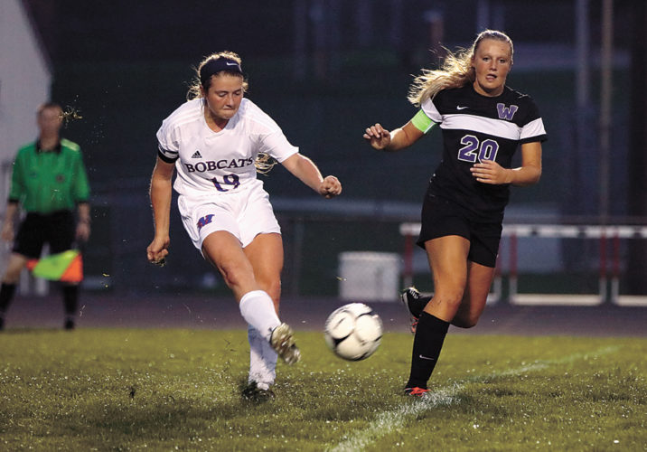 T-R PHOTO BY ADAM RING • Marshalltown's Aspen Chadderdon (19) passes the ball up the field ahead of Waukee's Rebecca Corbett (20) in the first half of Tuesday's match at Leonard Cole Field. Class 3A No. 2 Waukee blanked the Bobcats 6-0.