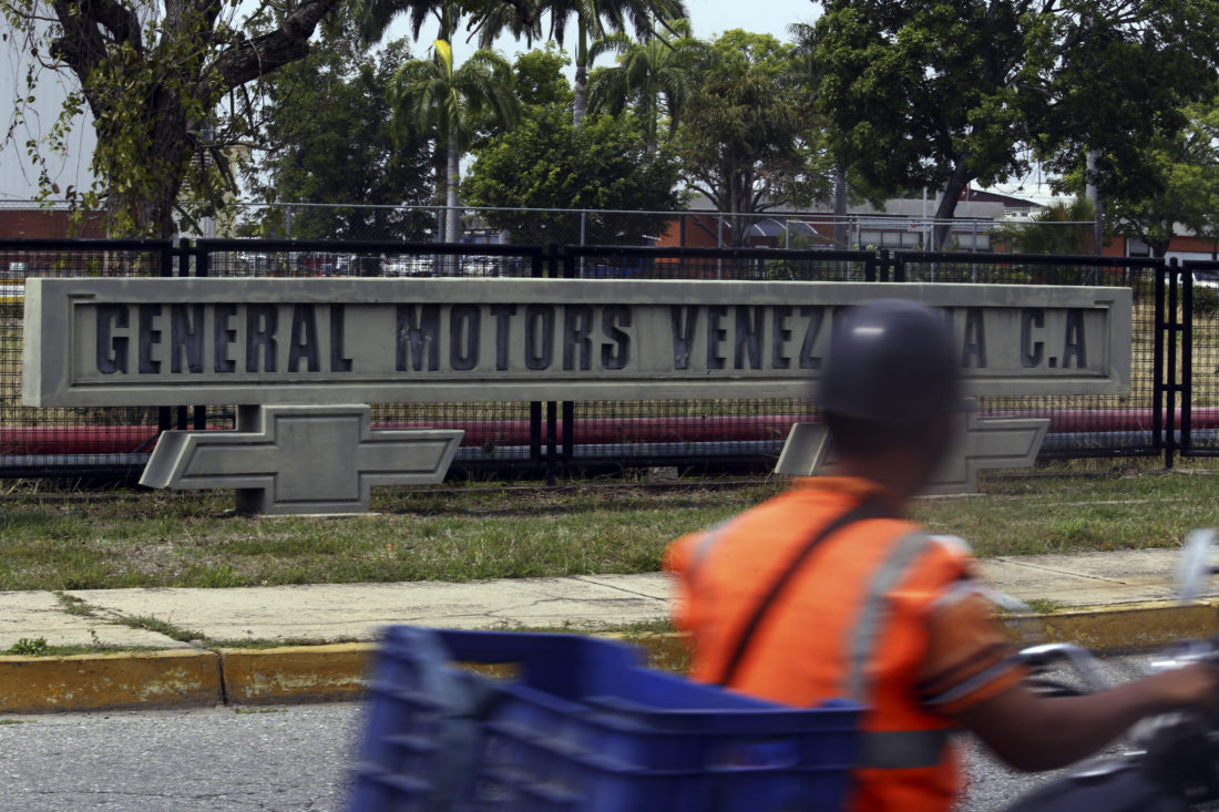 AP PHOTO A motorcyclist rides past the General Motors' plant in Valencia, Venezuela, Thursday. The company announced that it was shuttering operations in the country after authorities seized the factory on Wednesday.