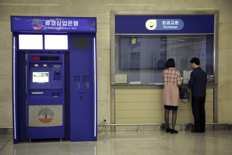 In this April 11, 2017 photo, a man and woman stand at a counter next to a Ryugyong Commercial Bank automated teller machine at the Sunan International Airport in Pyongyang, North Korea. No modern airport terminal is complete without an ATM, and Pyongyang's now has two. But they don't work, because of new Chinese sanctions, according to bank officials, and it's not clear when they will. ATMs are an alien enough concept in North Korea that those in the capital's shiny new Sunan International Airport have a video screen near the top showing how they work and how to set up an account to use them. The explanatory video is in Korean, but the machines, which are meant primarily for Chinese businesspeople and tourists, don't give out cash in the North Korean currency. (AP Photo/Wong Maye-E)