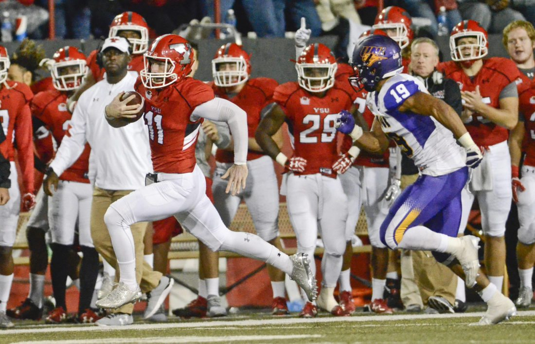 101516...R UNI @ YSU 5...Y-town...10-15-16... YSU QB #11 Trent Hosick rushes down the sideline in front of the YSU bench as UNI #19 Elijah Campbell pursues during 1st half action...by R. Michael Semple