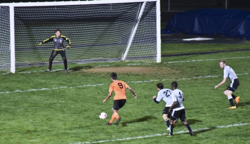 Tribune Chronicle / Joe Simon  Howland's Christopher Tvaroch (9) sets up before scoring a goal against Warren G. Harding goalkeeper Dimitri Callow on Wednesday. Harding players Michael Jordan (4) and Jody Hayes (27) follow the play. Howland won, 4-0.