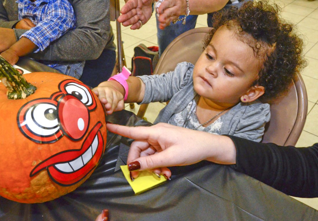 1020166...R WFM HARVEST 2...Warren...10-20-16... Eliza-Rose Moore, 2, of Warren, decorates her pumpkin with stickers with guidance from her mother Jessica Adams (out of view on right except for her hand) during the Warren Family Mission's Harvest Party Thursday afternoon...300 children were registered to attend the party....Novelis partner with the WFM to provide for the party....by R. Michael Semple