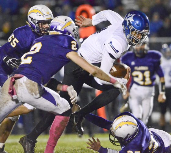 Tribune Chronicle / R. Michael Semple Lakeview's Jatise Garrison makes a reception and turns upfield as Champion defenders Chris Charney (65), far left, and Will Kovach (2), second from left, and Kenny Postlethwait, right bottom, go for a tackle during the first half of Friday's game in Champion.